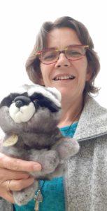 photo de Françoise de La Roche portant une peluche raton-laveur, mascotte de la promotion de formation Touch For Health : racoon.